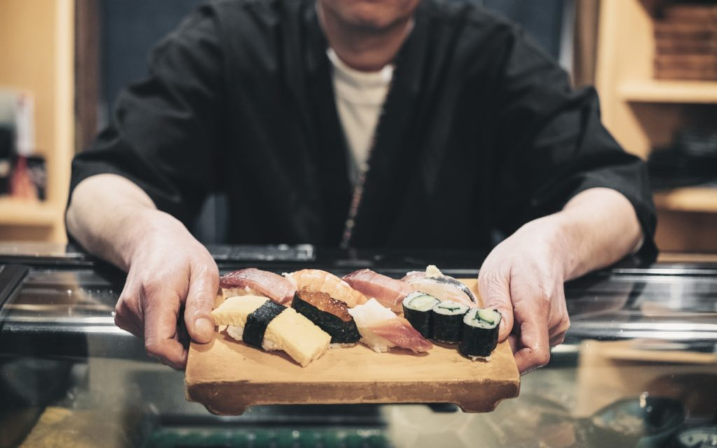 A sushi chef presenting a sushi plate as part of the Yokohama West Gate Restaurant map and guide