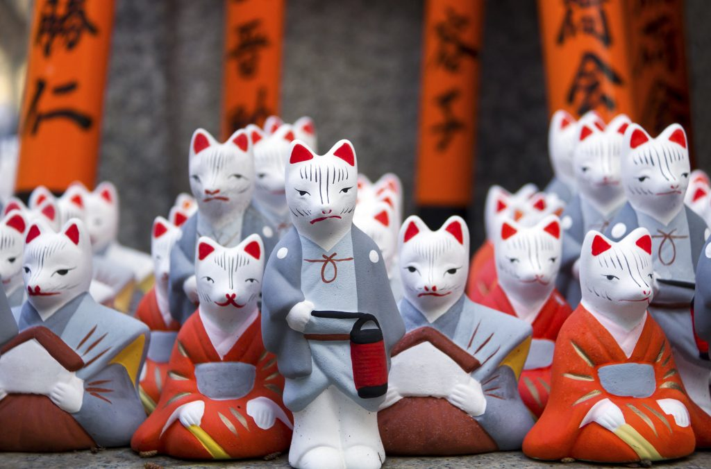 Little fox statues at Fushimi Inari Shrine in Kyoto, Japan