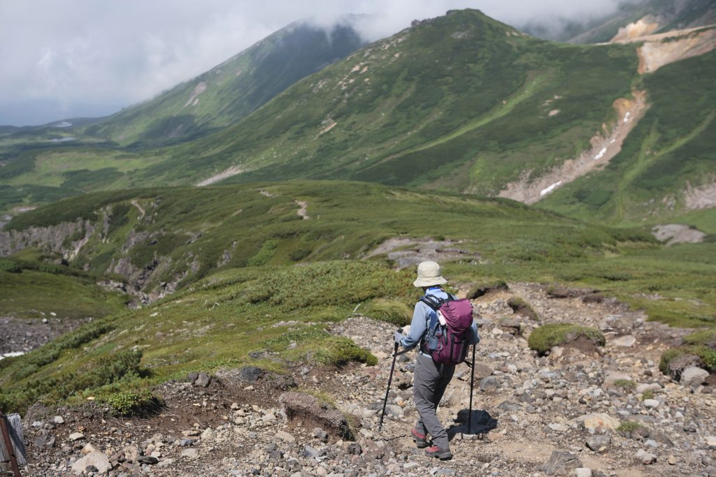 """A trekker walking down a trail in Daisetsuzan National Park in Hokkaido, Japan"""