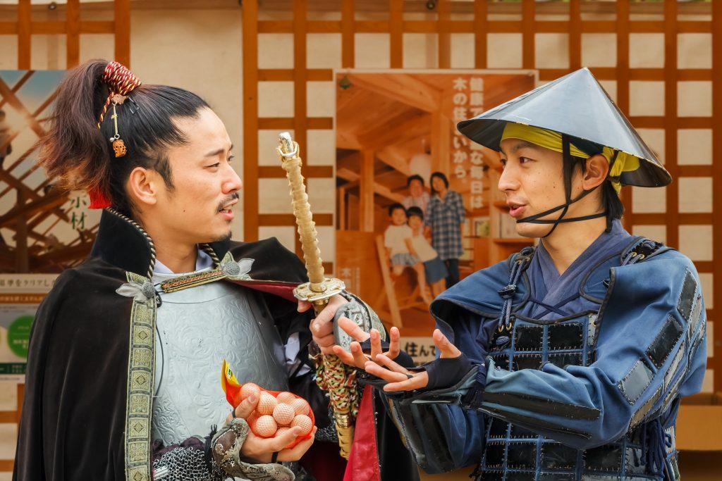 Nagoya, Japan - November 21 2013: Japanese vendor dresses old style warrior costume to promote his product at Nagoya Castle Fair