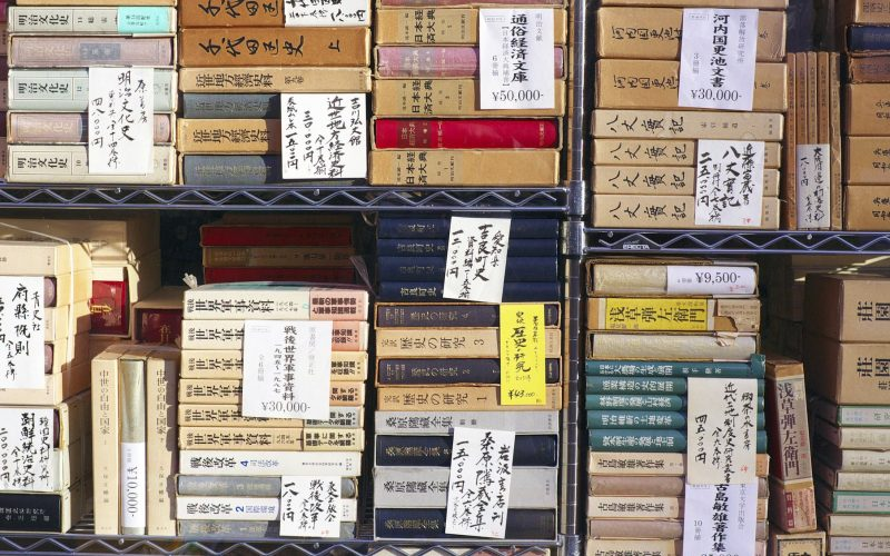Second-hand books stacked and priced in window display of bookshop in Jimbocho, Tokyo.
