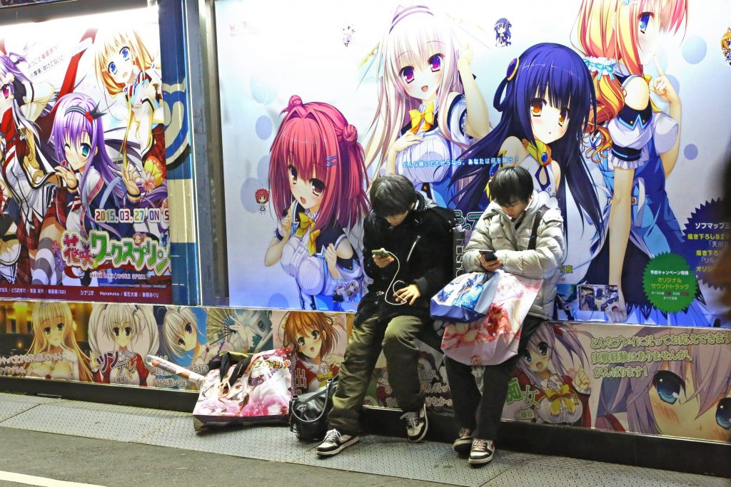 Tokyo, Japan - December 30, 2014: two teenagers use their portables in Akihabara district. On the wall behind them drawings of Manga.