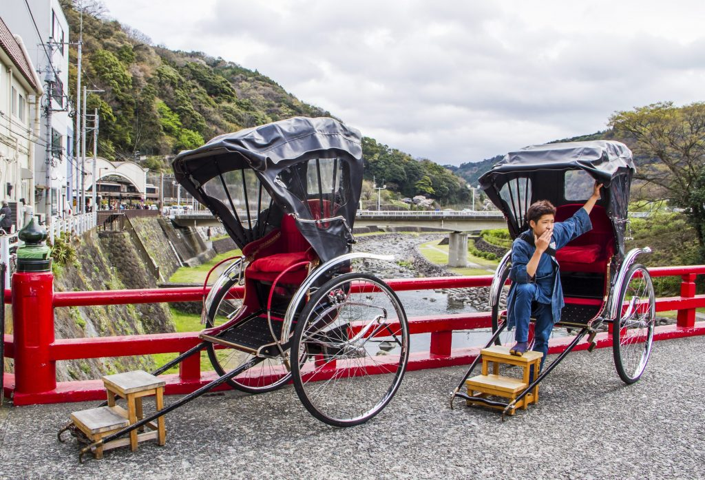 Hakone,Japan-April 3,2015 :Japanese boy take a pose with rickshaw waiting for customer in Hakone,Japan on April 3,2015.Rickshaw available in tourist attractive place .