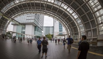Saitama, Japan - September 20, 2014: Saitamashintoshin Station. The majority of the people walk towards the Saitama Super Arena that can be glimpsed through the windows to the right. Ahead tall office buildings rise - including the NTT DoCoMo Saitama building on the right.