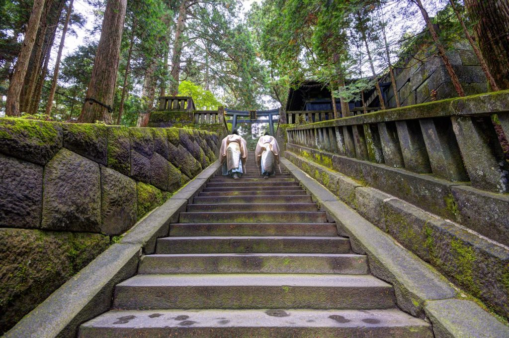 Nikko, Japan - November 11, 2012: Shinto priests ascend stairs at Toshogu shrine. The shrine holds the mausoleum of Tokugawa Ieyasu, founder of the Tokugawa shogunate, which ruled Japan for over 250 years until 1868.