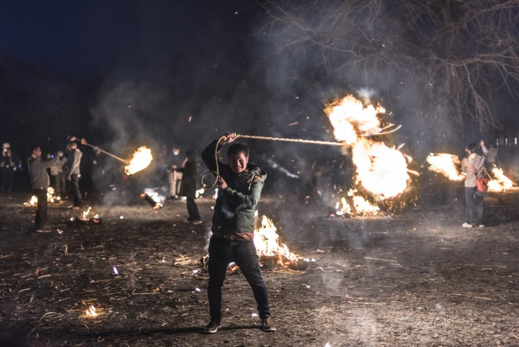 Aso, Kumamoto, Japan – March 21, 2015: Festivalgoer swinging a flaming bundle of straw at the Aso Shrine Fire Festival, Japan