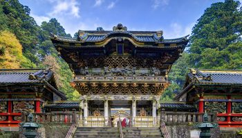 Nikko, Japan - November 1, 2012: A shinto priest sweeps under the Yomeimon gate at Tosho-gu Shrine. Founded in 1617, the remains of the first shogun Tokugawa Ieyasu are entombed here.