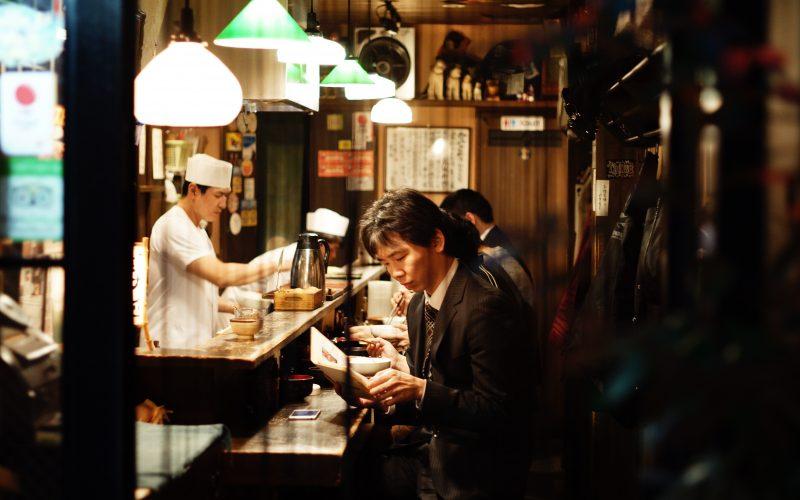 A man reading inside a small restaurant in Shinjuku, Tokyo