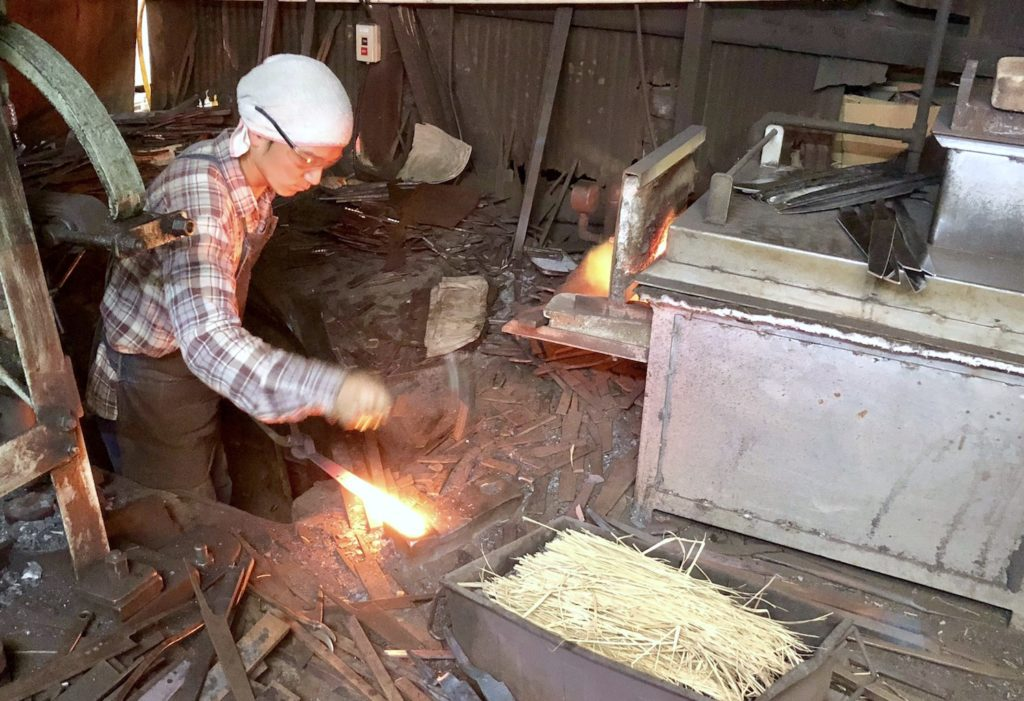 One of the craftsman forging a handmade steel knife in Sakai.