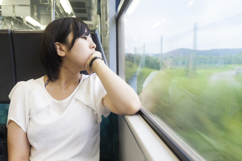 A young Japanese woman is traveling in a train and looking at the rural scene outside of the window.