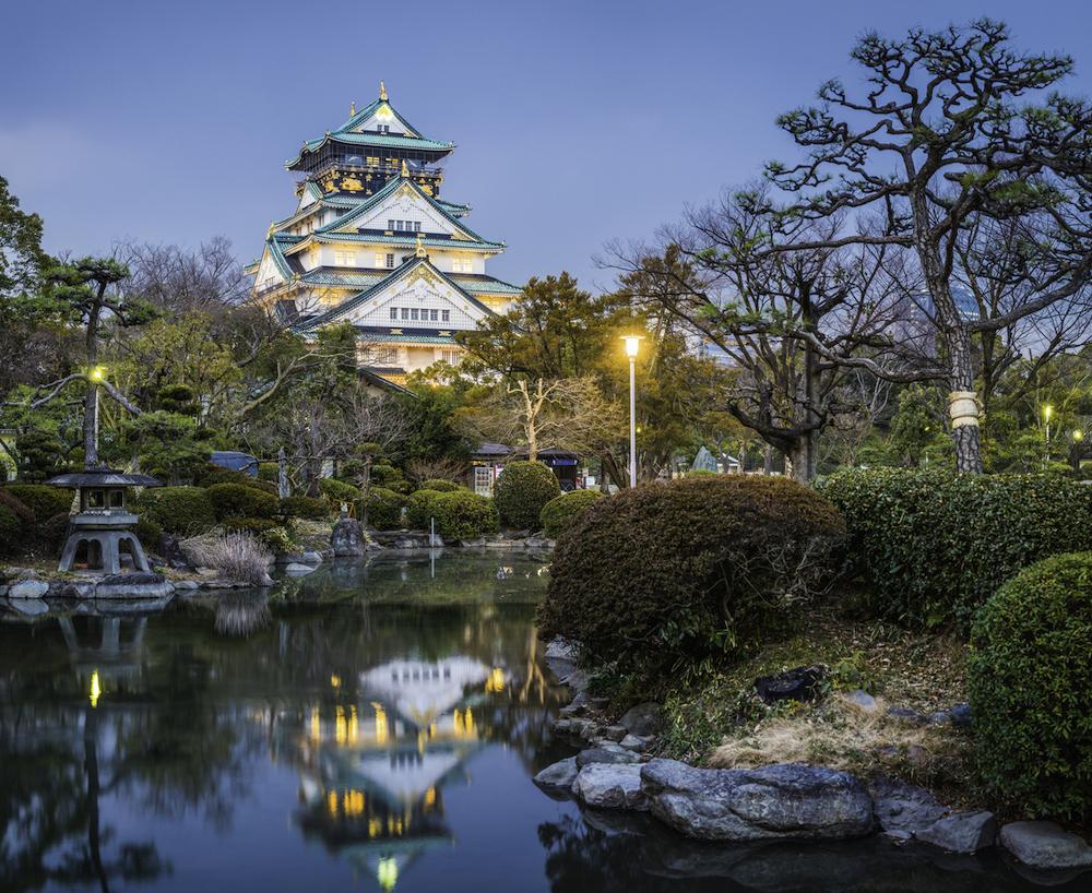 Osaka Castle illuminated at dusk reflecting in tranquil pond Japan