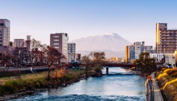 Mount Iwate Morioka city scene with buildings and promenade at Katakami river with warm sunset light